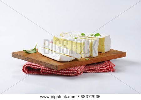 sliced cow's milk cheese, served on the wooden cutting board with fabric linen