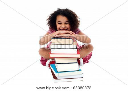 Cute School Girl Leaning Over Stack Of Books