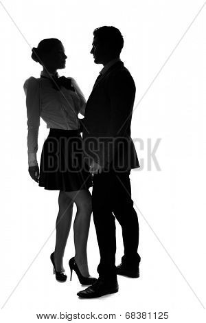 Silhouettes of an elegant romantic couple standing in profile in an embrace looking at each other, woman in stilettos and a miniskirt, man in a suit