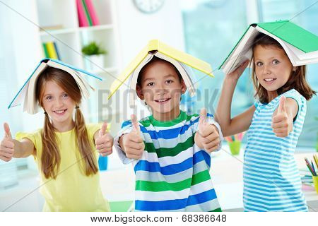 Portrait of happy classmates with books on their heads keeping thumbs up