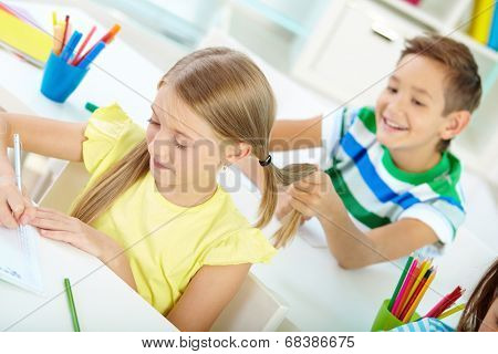 Portrait of lovely schoolgirl drawing at workplace while her schoolmate on background pulling her hair