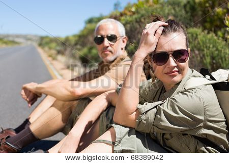 Hiking couple sitting on the side of the road looking at camera on a sunny day