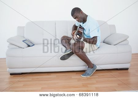 Casual man sitting on sofa playing the guitar with tablet pc at home in the living room