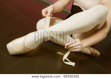 Ballerina tying the ribbon on her ballet slippers in the ballet studio