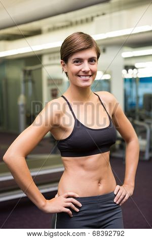 Fit brunette in black sports bra smiling at camera at the gym