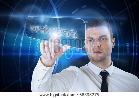 Businessman pointing to word weakness against digital background
