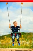 image of swingset  - Little blonde boy having fun at the playground - JPG