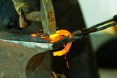 picture of blacksmith shop  - Making decorative element in the smithy on the anvil - JPG
