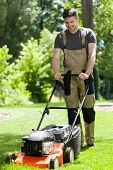 foto of overalls  - Man in work overalls mowing lawn vertical - JPG