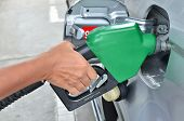 stock photo of tank truck  - A Man Pumping Gas In To The Tank - JPG