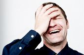 stock photo of single man  - Handsome man laughing with hand on the head - JPG