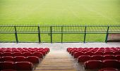 picture of bleachers  - Red bleachers looking down on football pitch on a clear day - JPG