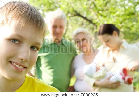 Boy Is On The Background Of Family