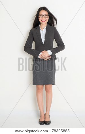 Full body happy Asian business woman standing on plain background.