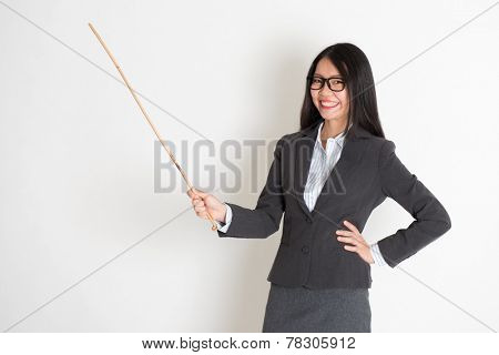 Asian female teacher smiling and holding a stick, standing on plain background.