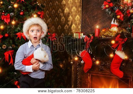 Cute seven year old boy stands with a gift by the Christmas tree at home. He is surprised. The magic of Christmas.