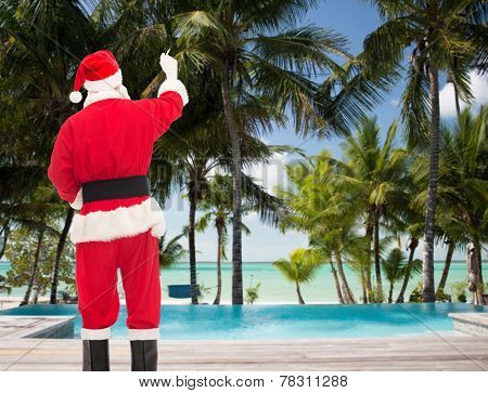christmas, holidays, travel and people concept - man in costume of santa claus writing something from back over tropical beach and swimming pool background