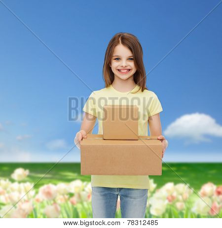 advertising, childhood, delivery, mail and people - smiling little girl holding cardboard boxes over flower field background