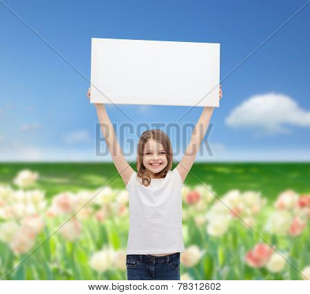 advertisement, childhood, happiness and people concept - smiling little child in white t-shirt holding blank board over blue sky and field of flowers background