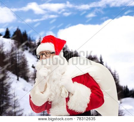 christmas, holidays and people concept - man in costume of santa claus with bag making hush gesture over snowy mountains background