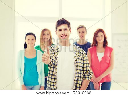 friendship, school and education concept - male student with classmates showing thumbs up gesture