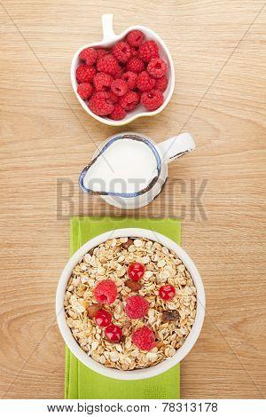 Healty breakfast with muesli, berries and milk on wooden table