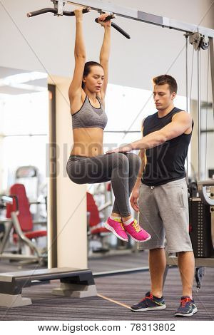 sport, fitness, lifestyle, teamwork and people concept - young woman with trainer hanging on bar and doing leg raises in gym