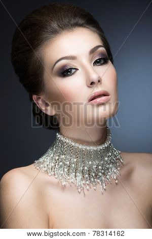 Beautiful woman with evening make-up and hairstyle and a large necklace around her neck. Beauty face