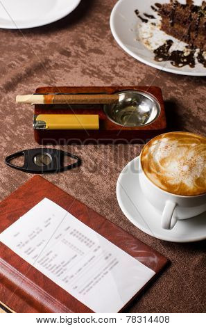 check, ashtray, cigar, lighter and coffee at restaurant table