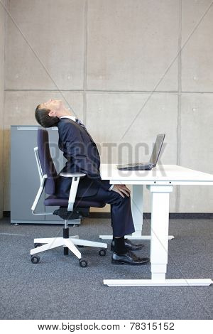 Office occupational disease prevention - business man exercising at workstation