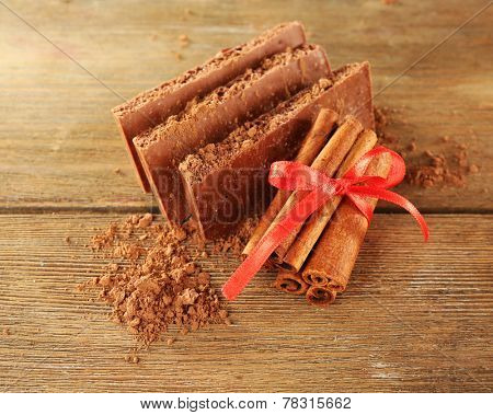 Porous chocolate with cocoa and cinnamon sticks on rustic background
