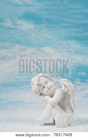 Dreaming or sad white angel on blue heaven background for a condolence card.