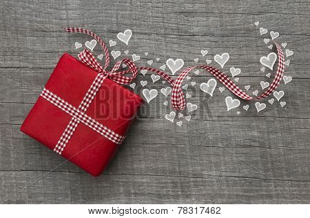 Red valentines present with checked ribbon and hearts on grey wooden background for a gift certificate.