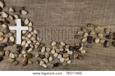 Cross of stones on wooden background for condolence or mourning cards.