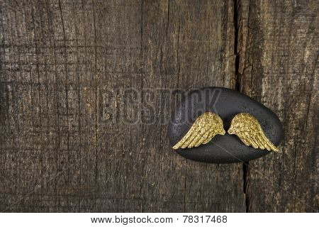 Golden angel wings with black stone on old wooden background for a card announcing somebodies death.