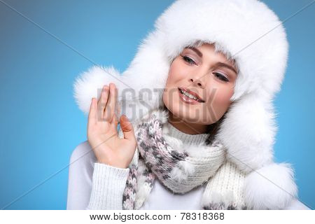 Beautiful merry sexual girl in a white fur cap and warm clothes on a blue background