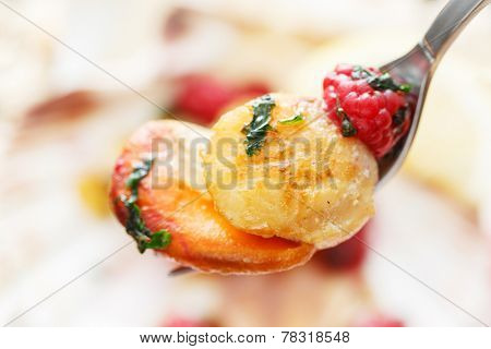 fried scallop with raspberries on a fork