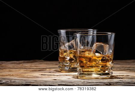 Whiskey drinks on wood with ice cubes