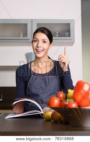 Happy Woman At The Kitchen Counter With Recipe Book