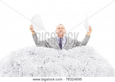 Desperate senior holding a torn file in a pile of shredded paper isolated on white background