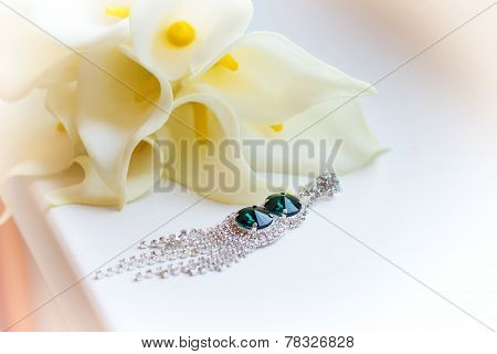 beautiful earrings on the windowsill near white flowers Kala wedding bouquet