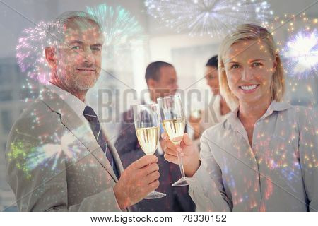 Business team celebrating with champagne and looking at camera against colourful fireworks exploding on black background