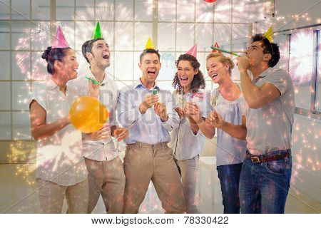 Casual business team celebrating with champagne and party poppers against colourful fireworks exploding on black background