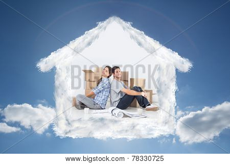 Couple sitting back-to-back against cloudy sky with sunshine
