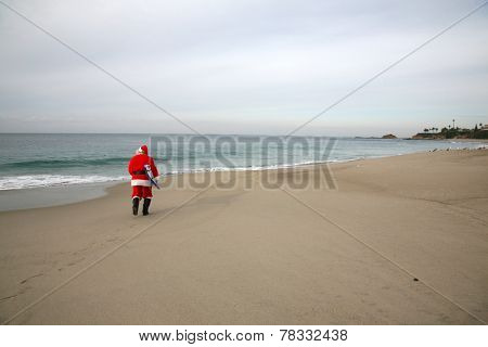 Surfing Santa Claus. A lonely Santa Claus walks on an empty beach with his Surfboard under his arm ready to go ride the waves alone. Reindeer and Elves do not surf so they leave Santa alone.