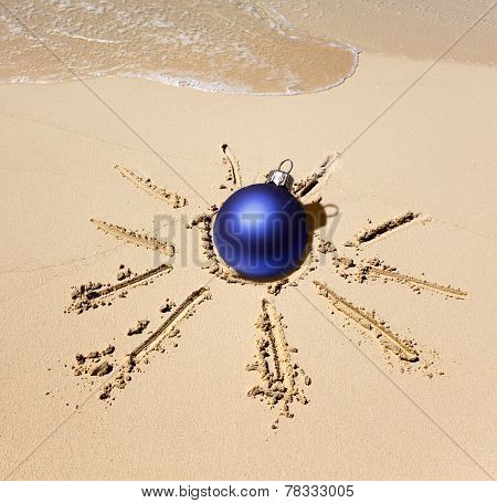 New Year's ball in the center of the sun drawn on sand on a beach