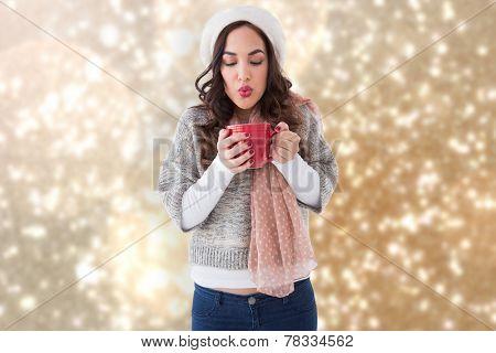 Brunette in winter clothes holding hot drink against blurred lights