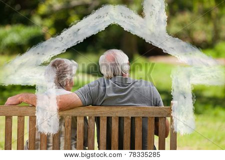 Couple sitting on the bench with their back to the camera against house outline in clouds