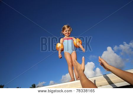 Little girl in swimsuit ready to jump from pontoon