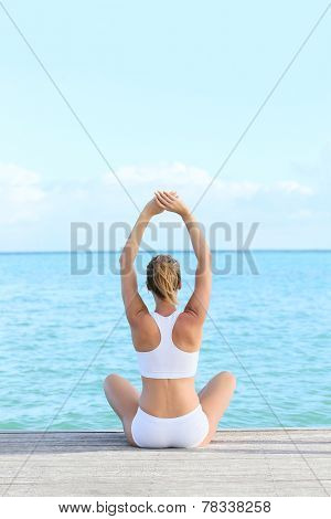 Back view of woman doing yoga exercises on pontoon